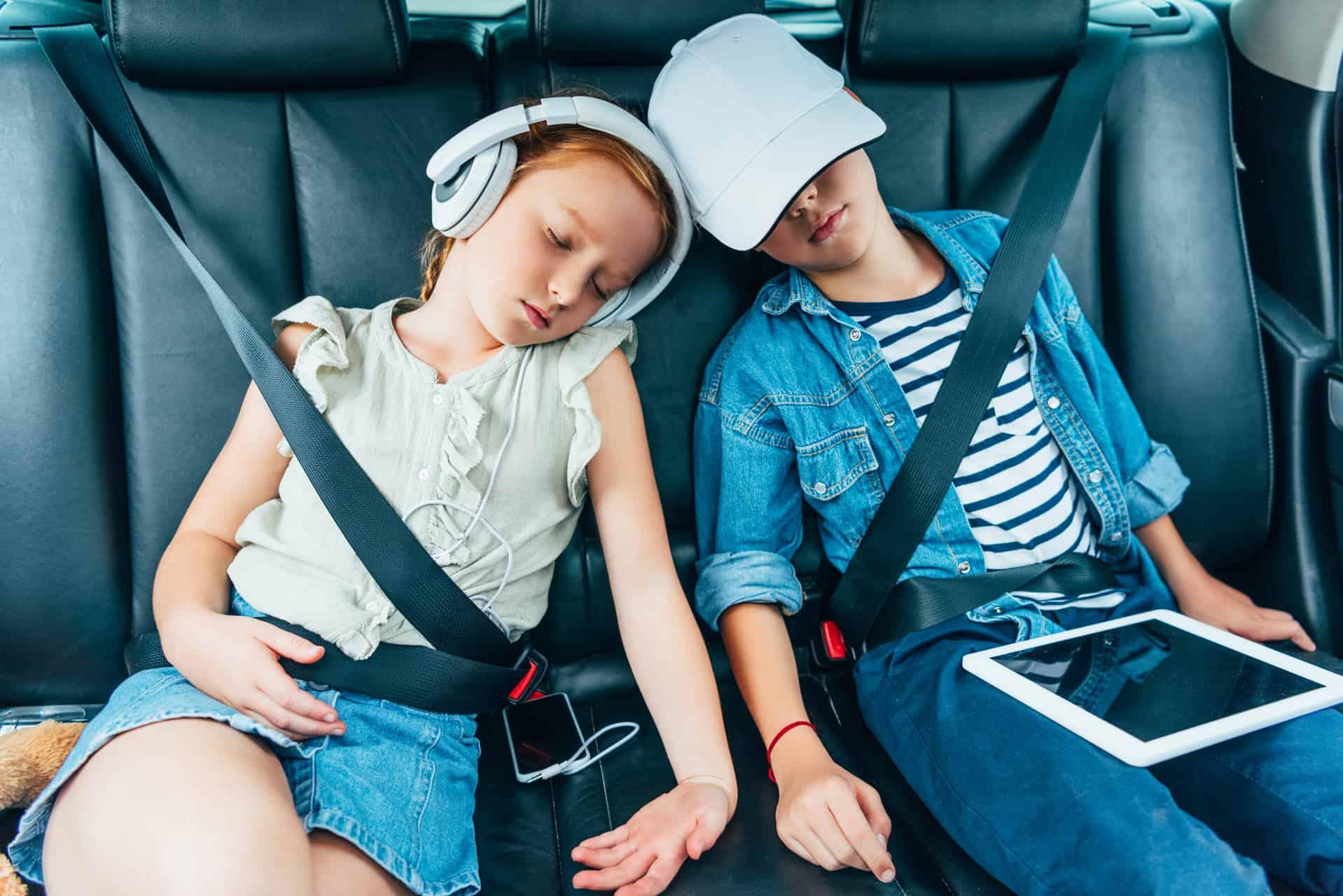 To Børn Sover På Bagsædet Af En Bil Med Smartphone Ipad Og Høretelefoner Ferie